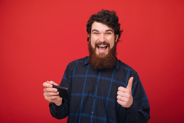 Un chico guapo con barba que usa un móvil mientras muestra el pulgar hacia arriba y