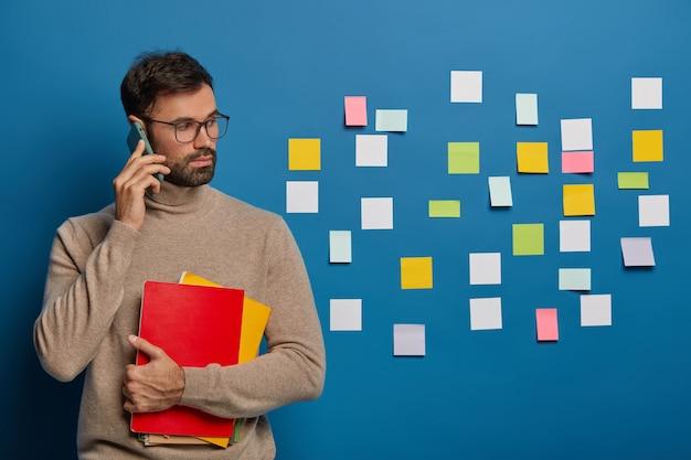 Chico guapo con barba sostiene un teléfono inteligente moderno cerca de la oreja, discute ideas de inicio, vestido con un cómodo jersey marrón