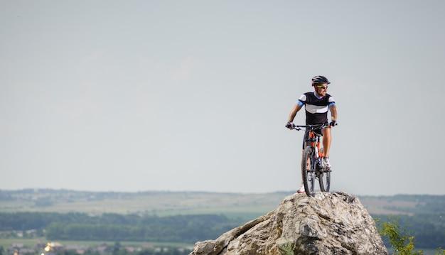 Chico guapo con bicicleta en la cima de la montaña