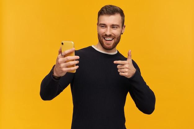 Chico guapo con cabello y barba morena. tiene piercing. vistiendo suéter negro. haciendo selfie. tiene videollamada. señalar con el dedo a la pantalla. mirando su teléfono, aislado sobre pared amarilla
