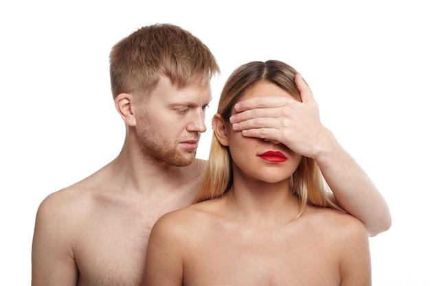 Chico guapo con cabello claro y rastrojo de pie sin camisa detrás de una atractiva mujer desnuda y tapándose los ojos con la palma. personas, relaciones, intimidad, sentimientos, vida sexual y cercanía