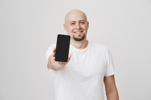 Chico guapo calvo en camiseta blanca que muestra el anuncio de la pantalla del teléfono inteligente sonriendo