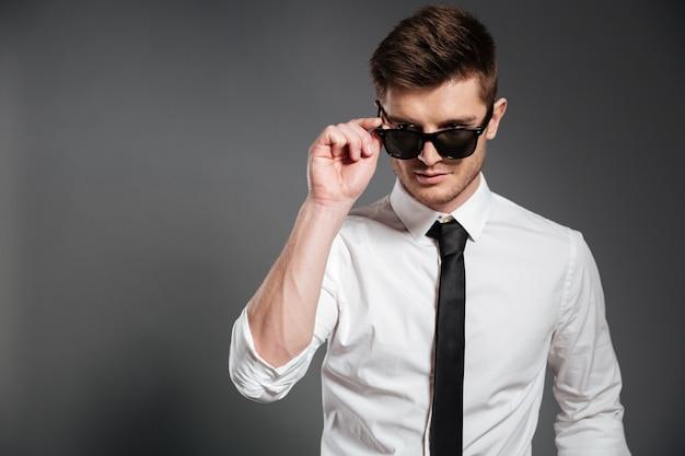 Chico guapo en camisa blanca de pie y posando con gafas de sol