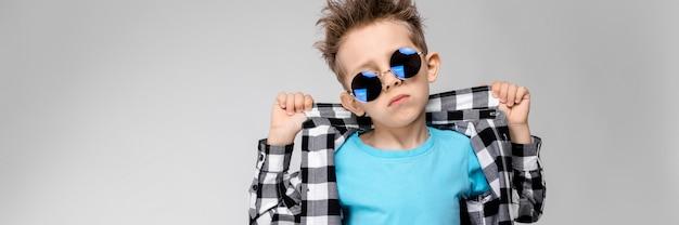 Un chico guapo con una camisa a cuadros, camisa azul y jeans está parado sobre un fondo gris