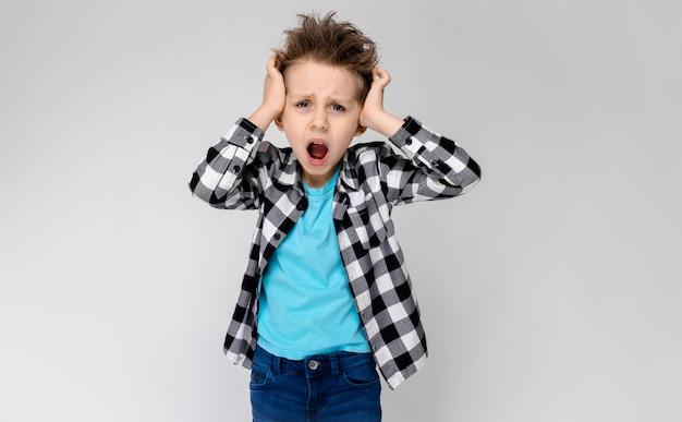 Un chico guapo con una camisa a cuadros, camisa azul y jeans