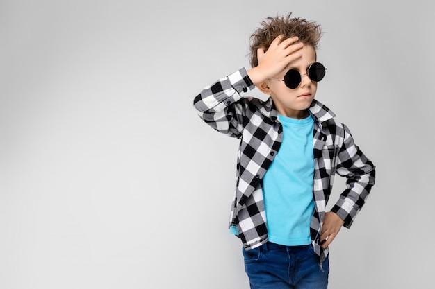 Un chico guapo con una camisa a cuadros, camisa azul y pantalones vaqueros se alza sobre un fondo gris. el niño lleva gafas redondas. chico pelirrojo sostiene su mano detrás de su cabeza