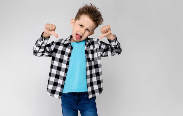Un chico guapo con una camisa a cuadros, una camisa azul y pantalones vaqueros destaca un gris. el niño cruzó los brazos sobre el pecho. niño mostrando el pulgar hacia abajo
