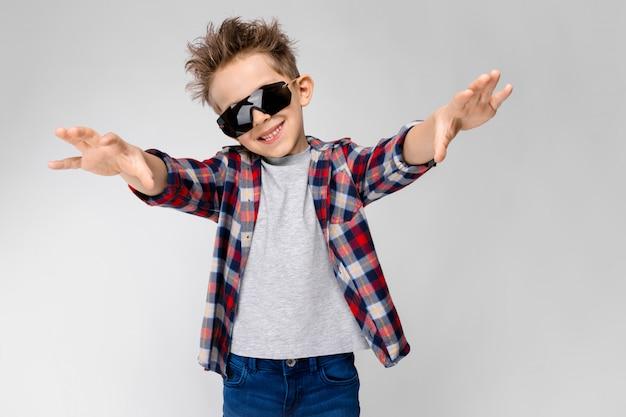 Un chico guapo con una camisa a cuadros, camisa gris y pantalones vaqueros se alza sobre un fondo gris. el chico de las gafas de sol negras. el niño estira los brazos hacia adelante.