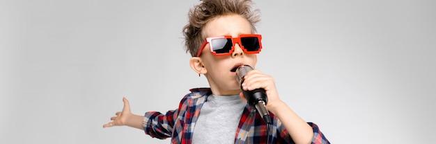 Un chico guapo con una camisa a cuadros, camisa gris y pantalones vaqueros se alza sobre un fondo gris. un niño con gafas de sol. chico pelirrojo canta en el micrófono