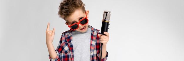 Un chico guapo con una camisa a cuadros, camisa gris y pantalones vaqueros se alza sobre un fondo gris. un niño con gafas de sol. el niño tiene un micrófono en la mano. el niño muestra una cabra mecedora.
