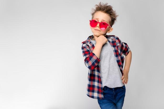 Un chico guapo con una camisa a cuadros, camisa gris y pantalones vaqueros se alza sobre un fondo gris. un niño con gafas de sol rojos. el niño lleva una mano a la barbilla.
