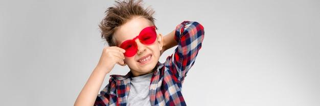 Un chico guapo con una camisa a cuadros, camisa gris y pantalones vaqueros se alza sobre un fondo gris. un niño con gafas de sol rojos. el niño sostiene sus anteojos