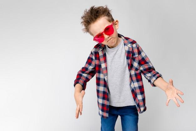 Un chico guapo con una camisa a cuadros, camisa gris y pantalones vaqueros se alza sobre un fondo gris. un niño con gafas de sol rojos. el niño tira de sus manos hacia adelante.