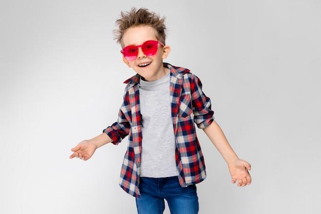 Un chico guapo con una camisa a cuadros, camisa gris y pantalones vaqueros se alza sobre un fondo gris. un niño con gafas de sol rojos.