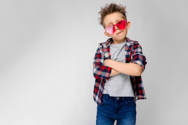 Un chico guapo con una camisa a cuadros, camisa gris y pantalones vaqueros se encuentra. un niño con gafas de sol rojos. el niño cruzó los brazos sobre el pecho.