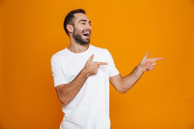 Chico guapo en camiseta apuntando con el dedo a un lado mientras está de pie, aislado en amarillo