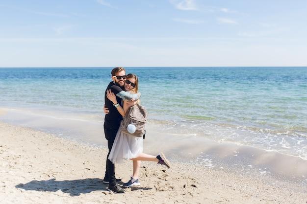 Chico guapo en camiseta negra y pantalones está abrazando a una mujer bonita con pelo largo cerca del mar