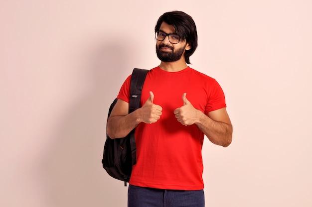 Chico guapo collage con mochila estudiante sonriente mostrando los pulgares para arriba con ambas manos