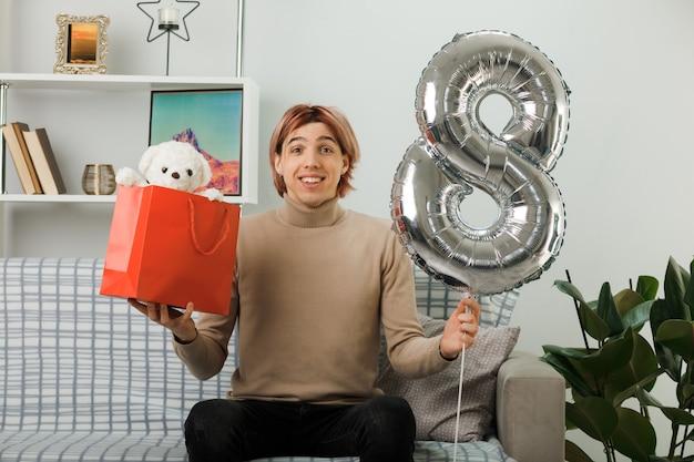 Chico guapo complacido en el día de la mujer feliz sosteniendo el globo número ocho con bolsa de regalo sentado en el sofá en la sala de estar