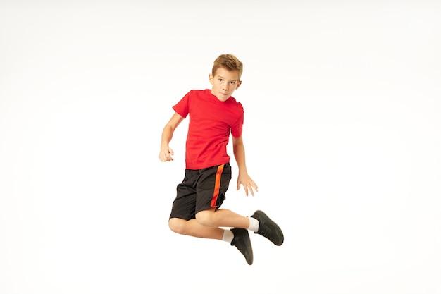 Chico guapo deportivo en pantalones cortos mirando a cámara y haciendo salto en estudio. aislado sobre fondo blanco