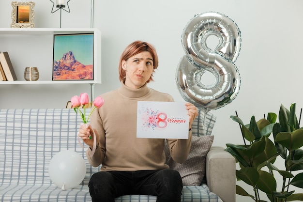 Chico guapo en el día de la mujer feliz sosteniendo flores con postal sentado en el sofá en la sala de estar