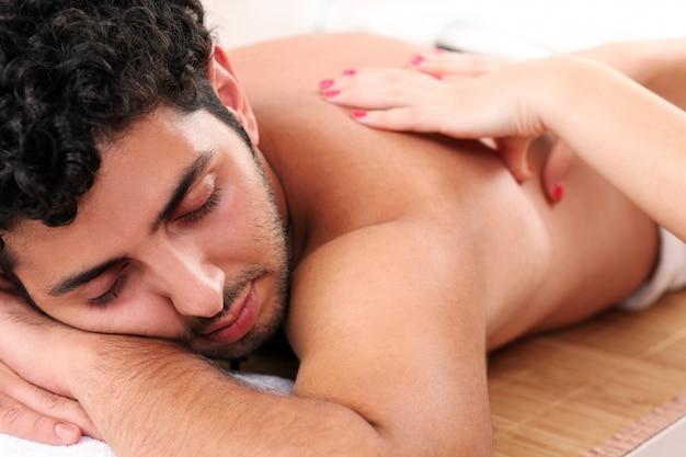 Chico guapo disfrutando de la terapia de masaje