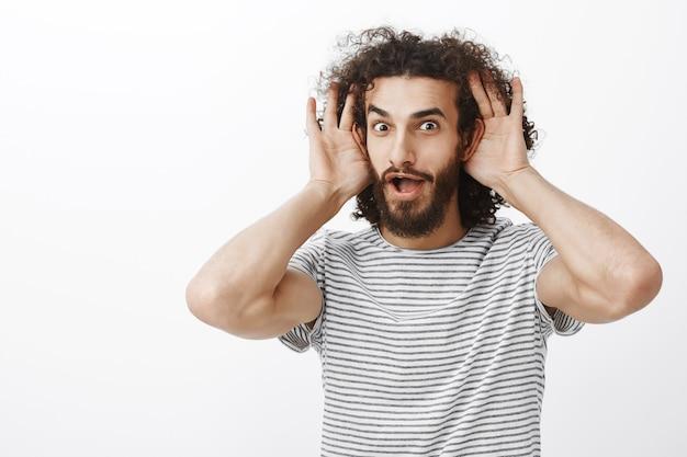 Un chico guapo e intrigado, emocionado al que le gustan los rumores nuevos e interesantes, sosteniendo las palmas cerca de las orejas y dejando caer la mandíbula por curiosidad