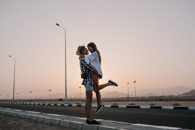 Chico guapo elegante con sombrero de moda sosteniendo a su novia delgada en blusa blanca, de pie en la carretera en las noches de verano. hermosa joven pareja abrazándose en una cita con increíble puesta de sol
