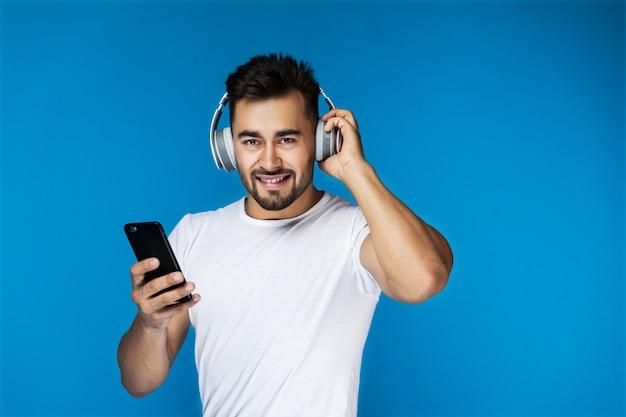 Chico guapo está escuchando música con auriculares y sosteniendo el teléfono celular en su brazo