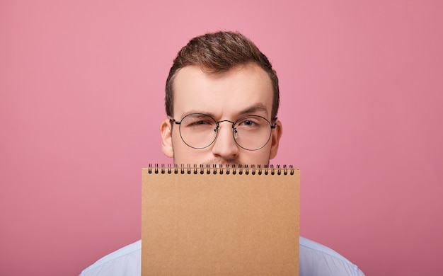 Chico guapo estudiante con gafas cubrió su rostro con un cuaderno marrón de hojas sueltas