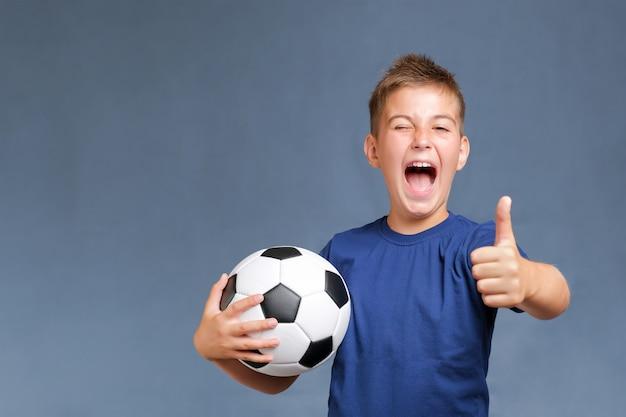 Chico guapo fan caucásico gritando sostiene un balón de fútbol y gesticula los pulgares para arriba