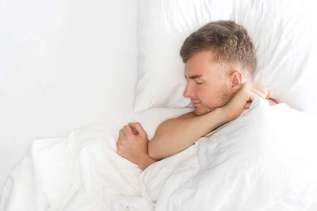 Chico guapo feliz, joven está durmiendo, teniendo buenos sueños, sonriendo, acostado sobre una almohada blanca, cubriendo con una manta. copia espacio, vista superior. sueño saludable, régimen diario, relajación, concepto de descanso.