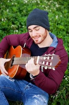 Chico guapo fresco tocando la guitarra en el exterior