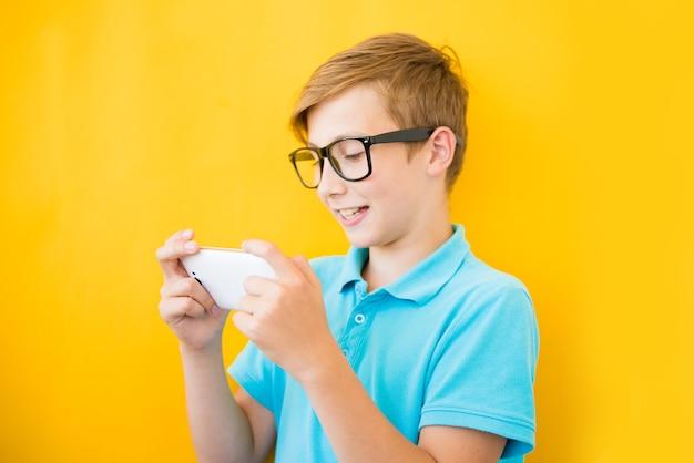 Chico guapo con gafas juega tableta. el concepto de mala vista, daño de los aparatos, miopía