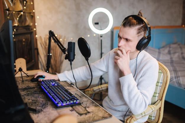 Chico guapo está grabando podcast con micrófono y creando contenido para el blog de audio que puso el hombre