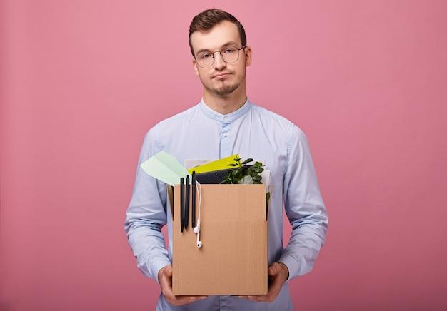 Un chico guapo y guapo con una camisa azul cielo está parado con una caja de cartón en sus manos