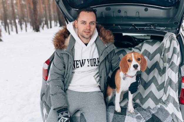 Chico guapo joven en un bosque nevado de invierno se sienta en el maletero de su coche