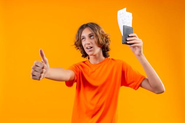 Chico guapo joven en camiseta naranja con billetes de avión buscando confianza mostrando pulgares arriba sonriendo alegremente de pie