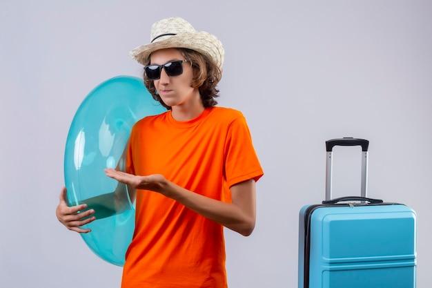 Chico guapo joven en camiseta naranja con gafas de sol negras con anillo inflable mirando confundido presentando con el brazo de la mano de pie con maleta de viaje sobre fondo blanco