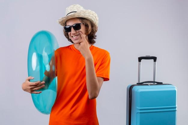 Chico guapo joven en camiseta naranja con gafas de sol negras con anillo inflable sonriendo alegremente apuntando con el dedo a su mejilla de pie con maleta de viaje sobre fondo blanco
