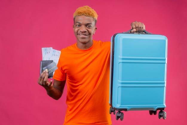 Chico guapo joven con camiseta naranja con maleta de viaje y billetes de avión sonriendo confiado positivo y feliz de pie sobre la pared rosa