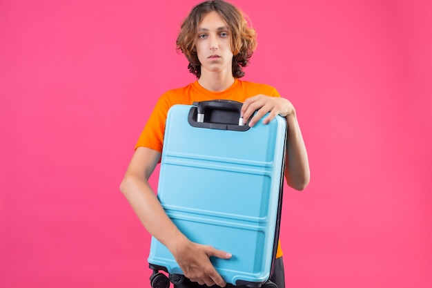 Chico guapo joven en camiseta naranja con maleta de viaje mirando a la cámara con cara triste de pie sobre fondo rosa
