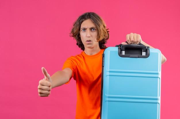 Chico guapo joven en camiseta naranja con maleta de viaje mirando a la cámara sorprendido mostrando los pulgares para arriba sobre fondo rosa