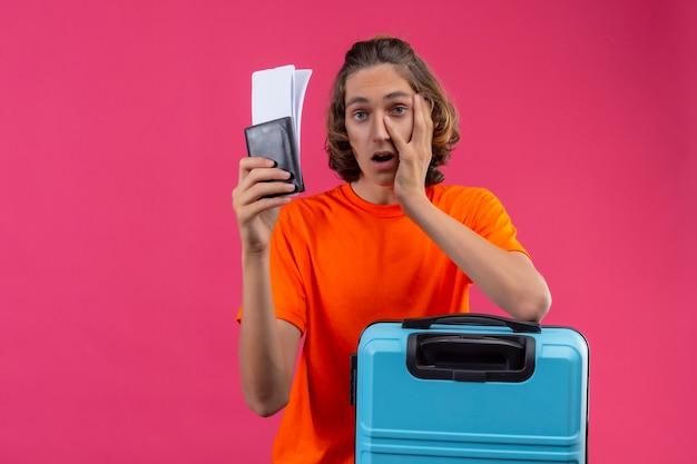 Chico guapo joven en camiseta naranja de pie con maleta de viaje sosteniendo boletos de avión con aspecto cansado y aburrido sobre fondo rosa