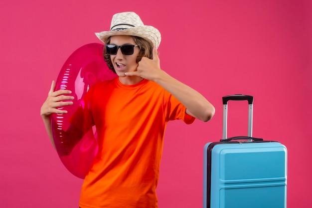 Chico guapo joven en camiseta naranja y sombrero de verano con gafas de sol negras con anillo inflable haciendo gesto de llamarme con la mano positiva y feliz de pie con maleta de viaje sobre rosa
