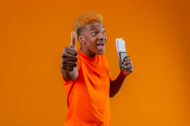 Chico guapo joven complacido con camiseta naranja con boleto aéreo sonriendo alegremente salido y feliz mostrando los pulgares para arriba sobre la pared naranja