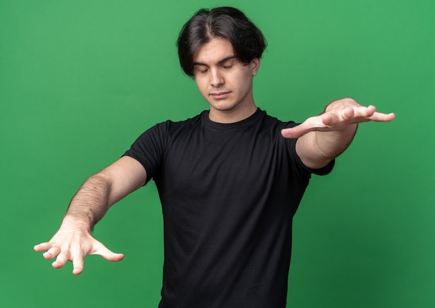 Chico guapo joven durmiendo con camiseta negra tendiendo las manos a la cámara aislada en la pared verde