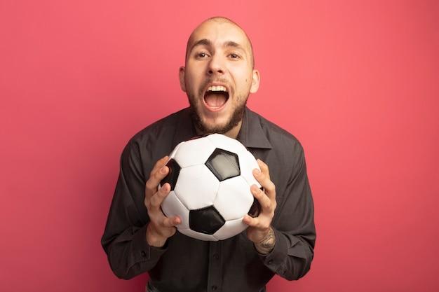 Chico guapo joven enojado sosteniendo la bola
