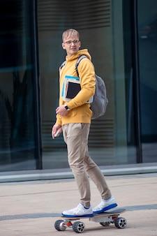Chico guapo, joven, hipster, estudiante o alumno con gafas en la cara montando en patineta eléctrica urbana moderna con mochila, libros y libros de texto. eco transporte, universidad, concepto de tecnología.