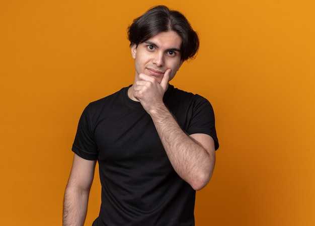 Chico guapo joven impresionado con camiseta negra agarró la barbilla aislada en la pared naranja